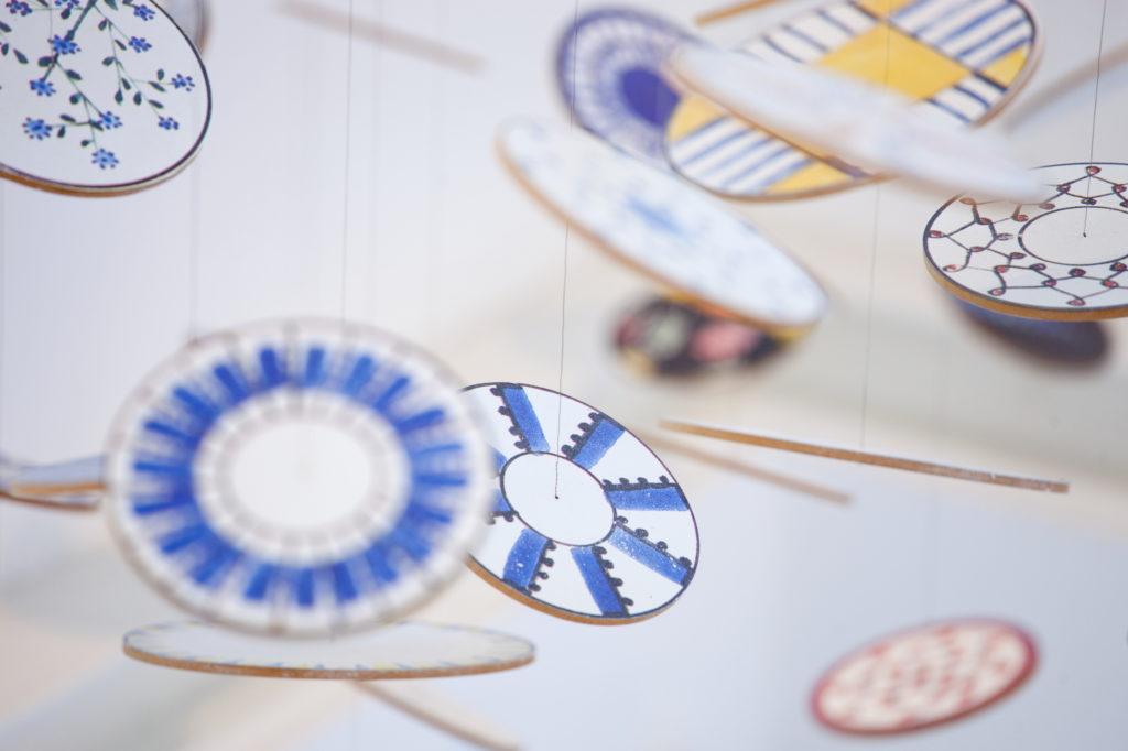 Ein Mobilé im Hedwig Bollhagen Museum ist zu sehen. Es hängen bunte Kreise in Blau, Gelb und Rot  an Schnüren.