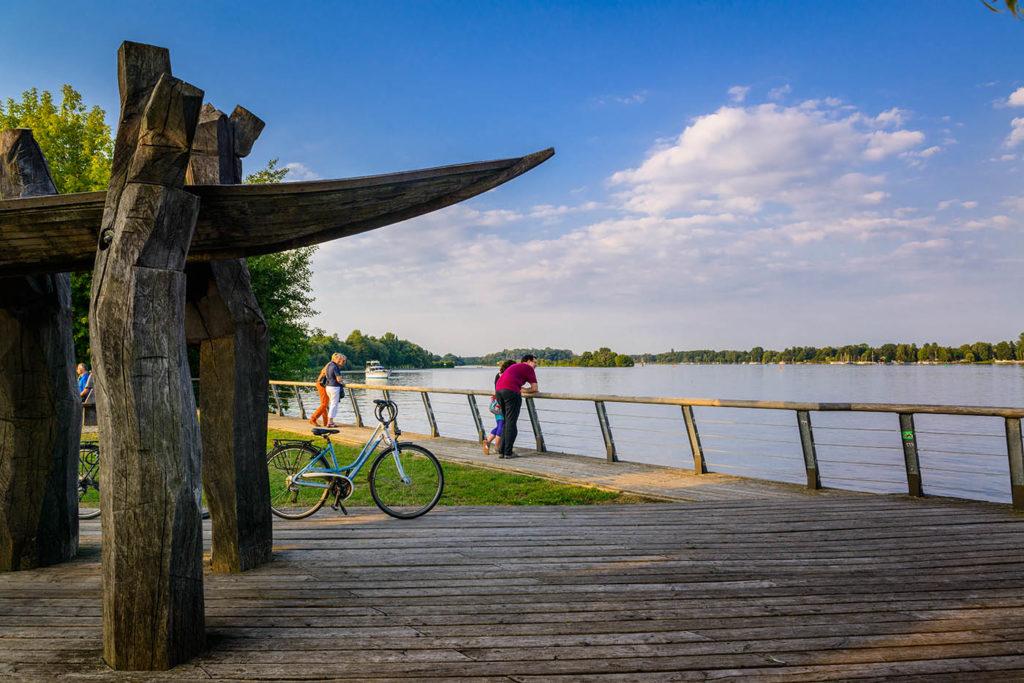 Uferpromende in Nieder Neuendorf. Menschen stehen am Ufer und schauen auf eine See. Blauer Himmel.
