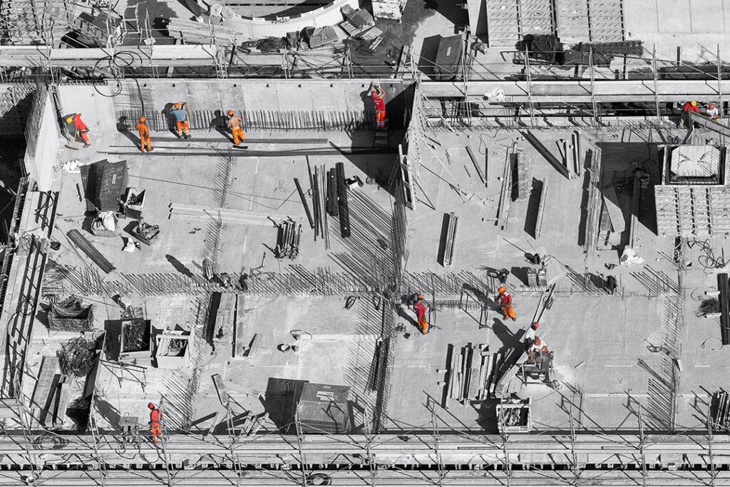 Aus der Vogelperspektive ist eine offenen Grundriss in schwarz weiß zu sehen. Acht Personen in orangener Bekleidung arbeiten an dem Aufbau der Gebäudes.