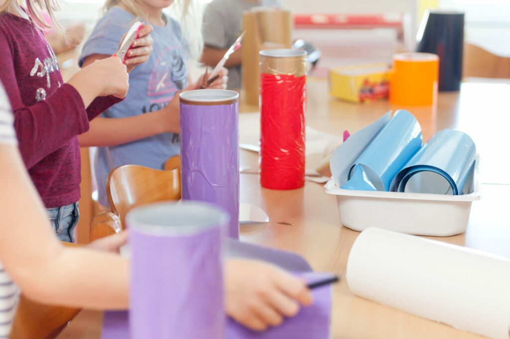 Kitakinder basteln. Es sind 3 Kinder zu sehen, die mit Scheren buntes Papier ausschneiden und Rollen bemalen.